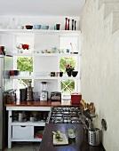 Eine Patchworkküche mit schlicht-raffinierter Regalkonstruktion vor dem Fenster
