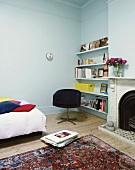 Ein alter Orientteppich vor dem Kamin im hellblauen Wohnzimmer mit Wandregal und Dielenboden