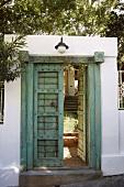 Eine altertümliche Eingangstür zum Vorgarten mit Metallsprossen und feiner Schnitzerei am Türsturz