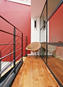 Ein Korbstuhl am Treppenabgang der hellen Galerie mit Holzboden