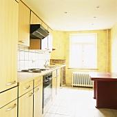 Eine schlichte 90er Jahre Einbauküche mit hellen Holzfronten gegenüber eines roten Holztisches