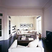 Blick in den stilvoll eingerichteten Wohnraum mit dunklem Parkettboden und Zierleisten an der Decke