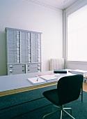 Alter Arztschrank hinter einem Schreibtisch in einer Praxis mit schöner Stuckdecke