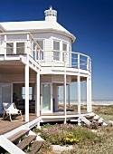 Ein strahlend weisses Haus am Meer, mitten in einer Blumenwiese