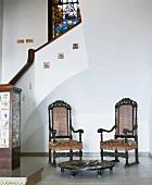 Zwei antike Stühle mit Bodentisch am Absatz eines historischen Treppenhauses mit Mosaikdetails und Fenstermalerei