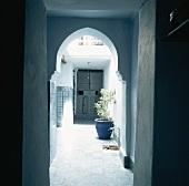 Blick in den Eingangsbereich eines orientalischen Hauses, mit traditoneller Arkade und Holztür