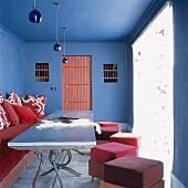 Schlichte, rote Polstermöbel an einem antiken Metalltisch bilden einen starken Kontrast zu dem blauen, traditionellen Wohnraum
