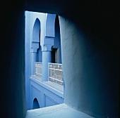 Blick durch eine Wandöffnung auf den blauen Arkadengang eines orientalischen Wohnhauses