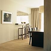 Klassisch gehaltenes Esszimmer in Cremetönen mit Frühstückstheke und Esstisch