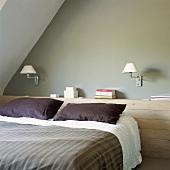 Ein holzvertäfelter Wandvorsprung dient am Kopfteil des Bettes als Ablagefläche
