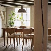 Einfache Holzmöbel bilden den Essplatz in einem traditionellen Fachwerkhaus mit typischer Holzbalkendecke