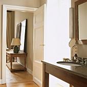 Durch die geöffnete Tür fällt der Blick vom Badezimmer in einen Nebenraum des elegant eingerichteten Wohnhauses