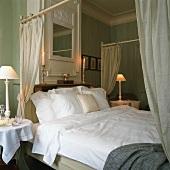 Ein gemachtes Himmelbett in einem klassisch-eleganten Schlafzimmer mit Stuckdecke