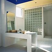 Eine Wand aus Glasbausteinen trennt die Dusche vom weiss gefliesten Badezimmer mit gemauertem Waschtisch ab