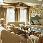 Rustikale Gemütlichkeit in einem Wohnzimmer mit Natursteinwand und weisser Holzbalkendecke