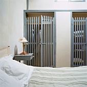 Zwei Einbauschränke mit halbtransparenten Holztüren im Schlafzimmer eines alten Bauernhauses