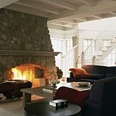Ein rustikaler Steinkamin bildet das Herzstück des klassisch möblierten Wohnzimmers mit Holzbalkendecke