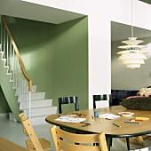 Kinderstühle und ein Vintagetisch mit Buntstiften in einem grünen Wohnraum