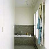 Mosaikfliesen ziehen sich vom Boden über die Badewanne bis zur Wand und werten das schlichte Badezimmer auf