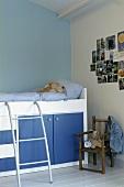 Ein rustikales Stühlchen neben einem Hochbett mit Stauraum im Kinderzimmer