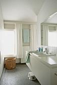 Ein schlichter, weisser Waschtisch im Badezimmer mit Mosaikfliesenboden
