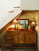 Schöne alte Holzkommode mit Dekoration in der Treppennische eines Landhauses