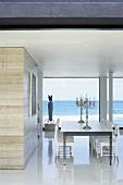 Essbereich mit Kandelabern und Biedermeierstühlen in moderner Architektur mit Meerblick durch die Panoramafensterfront