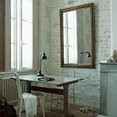 Ein antiker Holztisch und zwei weisse Stühle vor einem Wandspiegel in der Ecke eines Raums mit Backsteinwänden