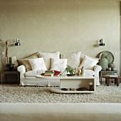 Weisses Sofa mit vielen Kissen und antike Tongefäße und Sklupturen auf Beistelltischen