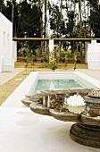 Gepflegter Aussenbereich mit kleinem Pool und traditionellem Holzbrunnen