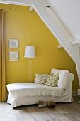 Chaise Longue mit Husse im gelben Dachgeschosszimmer mit Dielenboden