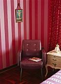 Retrosessel und barockes Nachttischchen vor roter Streifentapete