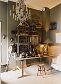 Eine Sammlung von Käfigen, ein Vogelhäuschen und diverse Utensilien auf einem abgenutzten Holztisch
