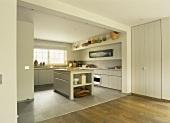 Kleine Korbsammlung in einer Vintageküche mit schlichten Holzfronten und Küchenblock