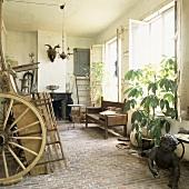 Alte Pferdekutsche und Holzbank in einer rustikalen Werkstatt mit Steinboden und elegantem Kamin