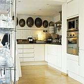 Antike Servierglocken zieren die Steinwand der weißen, minimalistischen Küchenzeile
