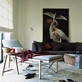 Schlichte, moderne Liege und rustikaler Beistelltisch auf einem Kuhfell im Wohnzimmer