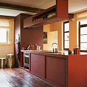 Freistehende, kubische Küchenzeile in Rot in rustikalem Ambiente mit Deckenbalken und Dielenboden