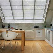 Esstisch und Designerstühle in einer Küche mit großem Dachfenster im Dachgeschoss