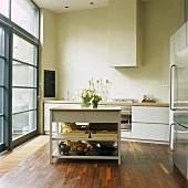 Küchenblock in einer modernen, minimalistischen Küche mit Parkettboden und Fensterfront