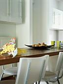 Detail einer Küchentheke mit Kunststoffstühlen und Geschirr