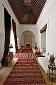 Schlauchförmiger Wohnraum im marokkanischen Stil mit roten Läufern und vielen Sitzgelegenheiten