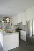 Moderne, offene Küche mit weissen Schränken, Marmorplatten und Edelstahlkühlschrank
