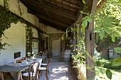 Einfacher Holztisch und Thonetstühle auf der rustikalen, überdachten Terrasse eines alten Bauernhauses