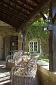 Klassische Korbstühle auf der rustikal überdachten Terrasse eines alten Bauernhauses