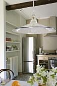Weissblaue Küchenleuchte über dem Esstisch und Blick auf den Edelstahlkühlschrank einer modernen Küchenzeile