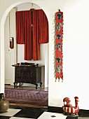 Eingangsbereich mit kleiner, chinesischer Kommode und rotem, dekorativ drappiertem Kimono