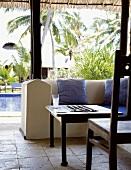 Gepolsterte Steinbank und antiker Holztisch auf der strohüberdachten Terrasse einer Hotelanlage