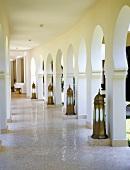 Ein orientalischer Arkadengang mit Mosaikfliesenboden und antiken Bodenlaternen vor den Säulen