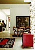 Biedermeierstühle am Esstisch vor einem abstrakten Ölgemälde im offenen Wohnraum mit roter Antikkommode